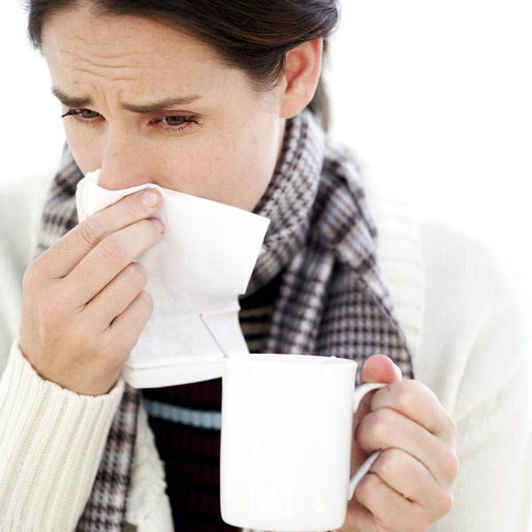 Woman Holding a Mug with a Handkerchief to Her Nose --- Image by © Royalty-Free/Corbis